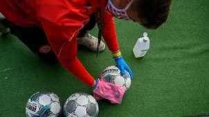 Recogepelotas limpiando el balón en la vuelta de la Bundesliga tras el coronavirus