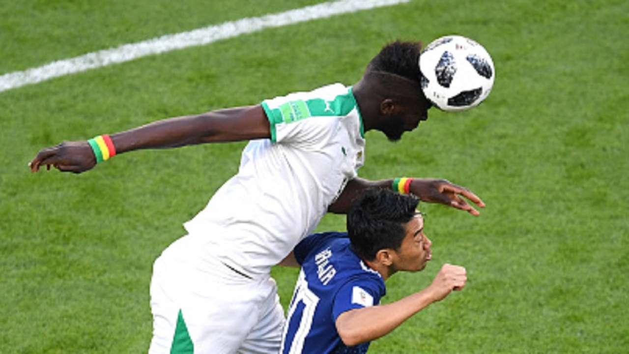 Salif Sane of Senegal wins a header over Shinji Kagawa of Japan during the 2018 FIFA World Cup Russia