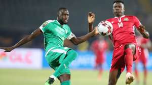 Cheikhou Kouyate of Senegal clears ball from Michael Olunga of Kenya.