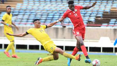 Francisco Muchanga of Mozambique tackles Michael Olunga of Kenya and Harambee Stars.