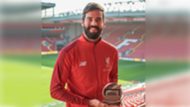 Liverpool's Alisson collecting his Goalkeeper of the Year trophy from Goal