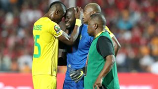 Edmore Sibanda (c) of Zimbabwe leaving the field after being injured.