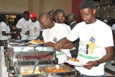 Gor Mahia players serve food after being hosted to luncheon by Football Kenya Federation
