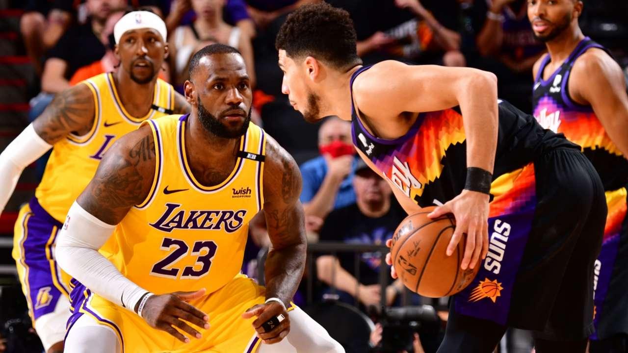 Lakers forward LeBron James defends Suns guard Devin Booker