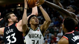 Giannis Antetokounmpo scores over three Raptors in Game 1.
