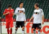 Germany's midfielder Michael Ballack (C) has a disagreement with Germany's striker Lukas Podolski (R)