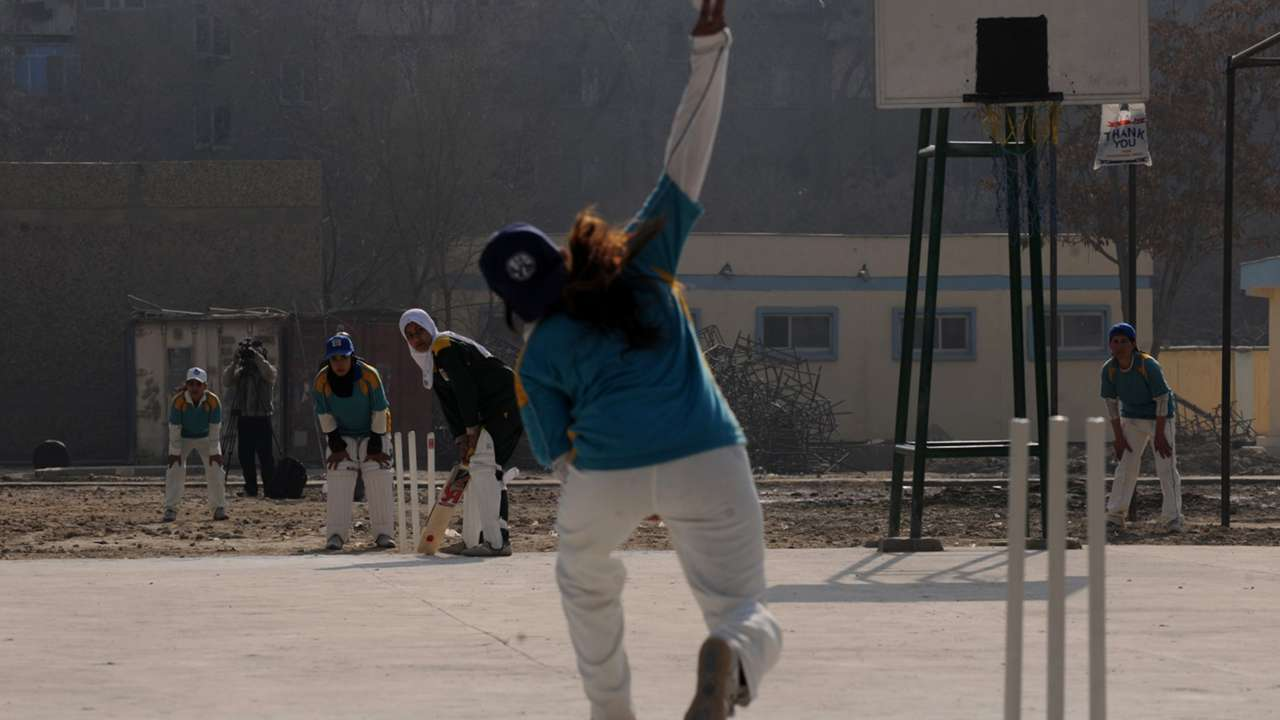 Afghan girls play cricket on the school grounds in Kabul.